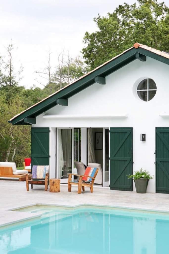 Общий вид на белый дом с зелеными ставнями от дизайнера интерьера Marta de la Rica